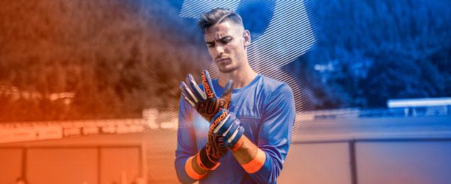 Modelo probandose unos guantes Reusch color azul con detalles de color naranja.