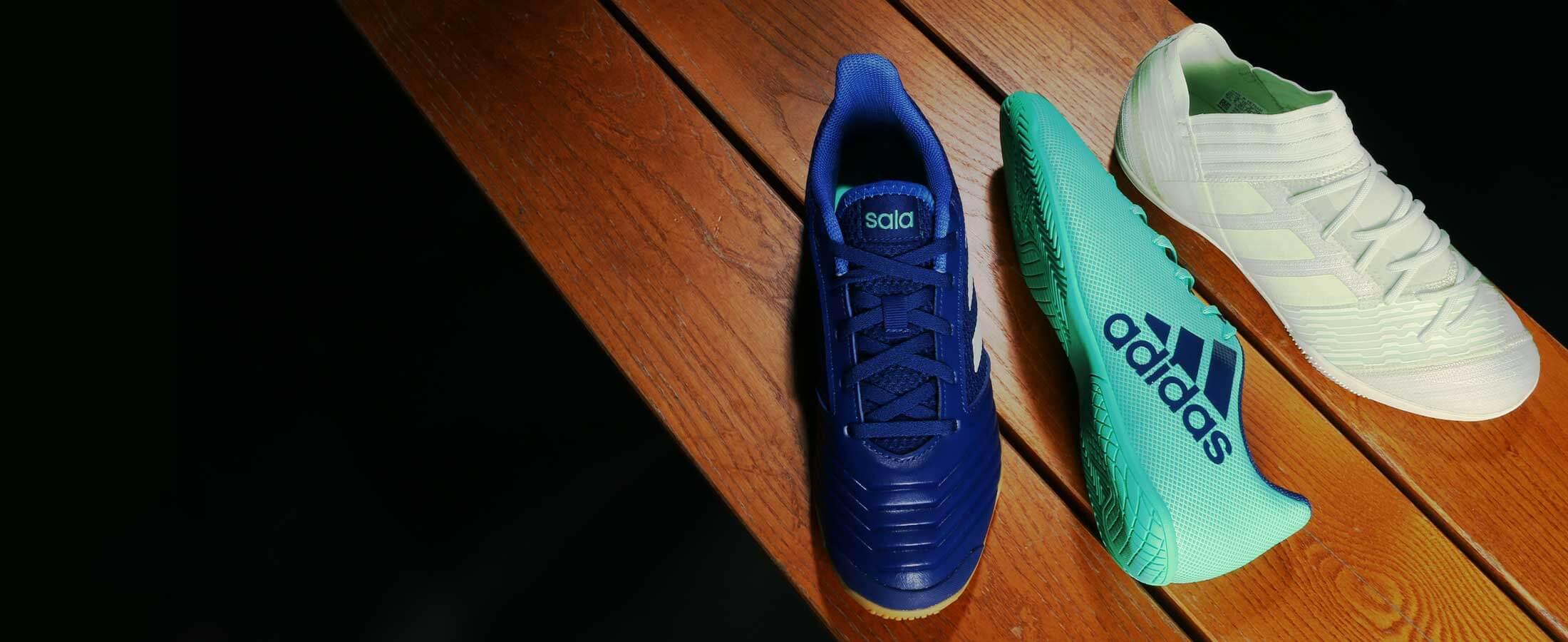 Zapatillas de fútbol sala adidas de la colección Cold Blooded sobre superfície de madera