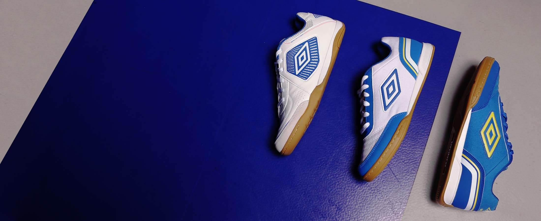 Tres zapatillas de fútbol sala Umbro sobre pista azul
