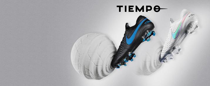 Aparecen dos botas de fútbol Nike tiempo, unas color blanco y otras en negro con detalles en azul.