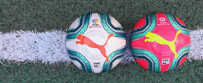 2 balones puma de La Liga Santander, el de la izquierda con un diseño que combina el color blanco con toques de azul y naranja que le dan un toque llamativo y el de la derecha una combinación de azul con fondo rosa llamativo con el logo de puma am