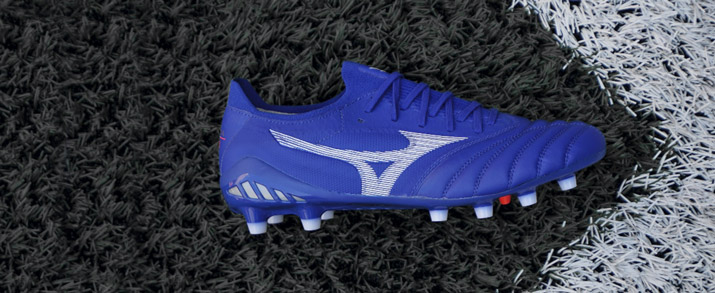 Botas de fútbol Mizuno, sobre cesped natural, color azul.