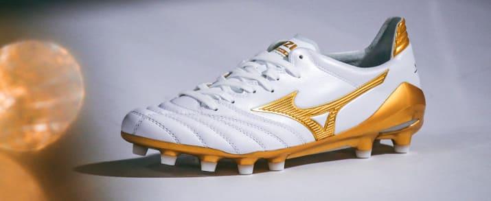 Botas de fútbol Mizuno, sobre cesped aritificial, Diseño sobrio en color blanco con pequeños detalles en dorado. Combina el estilo clásico con las necesidades del fútbol moderno.