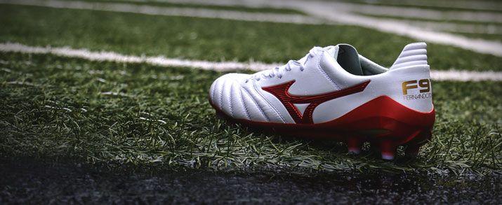 Botas de fútbol Mizuno, sobre cesped aritificial, diseño sobrio en color blanco, que se combina con rojo y pequeños toques de dorado.