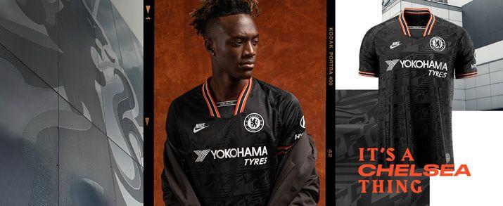 Camiseta de la tercera equipación 2020 Chelsea, color negro con unos gráficos inspirados en los años 90. Observamos detalles en color blanco y naranja en la zona de las mangas y cuello. Swoosh de Nike sportswear y escudo del Chelsea bordados.